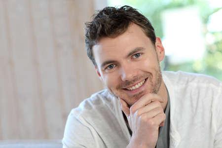 blonde yeux bleus: Portrait de jeune homme souriant se détendre dans le canapé Banque d'images
