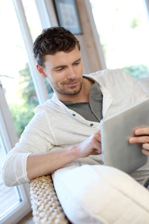 Man sitting in sofa with electronic tablet photo