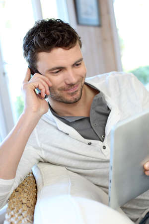 Man talking on the phone while using tablet photo