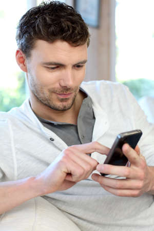 30 years old man: Young man using mobile phone to send short message