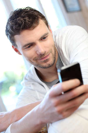 Young man using mobile phone to send short message photo