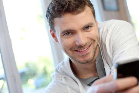blonde yeux bleus: Jeune homme utilisant un téléphone mobile pour envoyer des messages courts