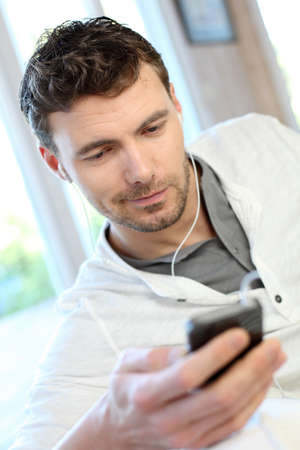 handsfree phone: Young man using mobile phone with handsfree headset Stock Photo