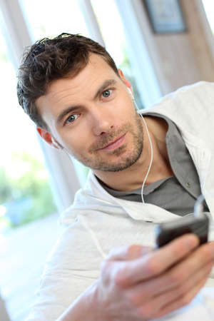 Young man using mobile phone with handsfree headset photo