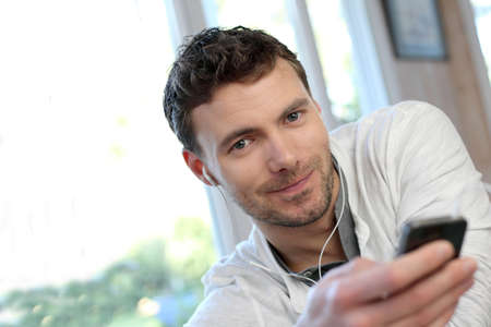 Young man using mobile phone with handsfree headset Stock Photo - 13806753
