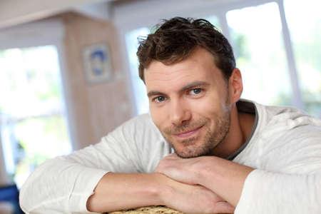 jeune vieux: Portrait de jeune homme souriant se d�tendre dans le canap� Banque d'images