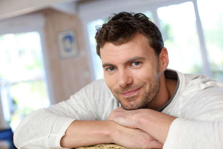 SATISFIED: Portrait of young smiling man relaxing in sofa Stock Photo