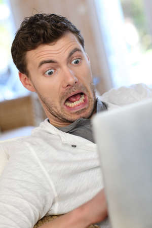 Portrait of scared man in front of electronic tablet photo