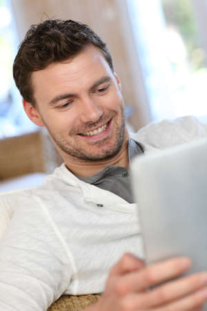 Portrait of young man relaxing in sofa with electronic tablet photo