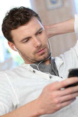 Portrait of young man listening to music with smartphone photo