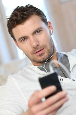 mobile headsets: Portrait of young man listening to music with smartphone