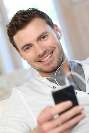 earbud: Smiling man using cellphone at home
