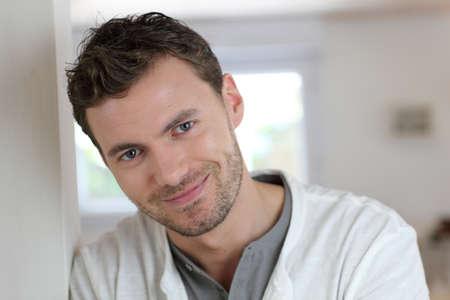 blonde yeux bleus: Portrait d'un homme beau se penchant sur le mur
