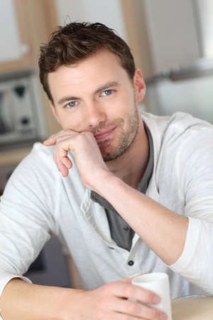 30 years old man: Portrait of handsome guy drinking coffee in home kitchen