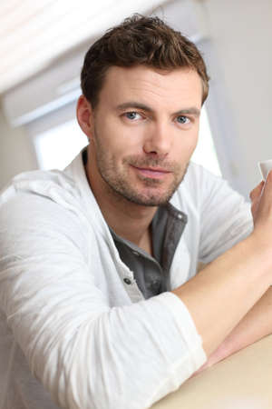 man drinking coffee: Portrait of handsome guy drinking coffee in home kitchen