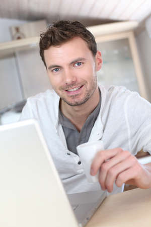 Man drinking coffee in front of laptop computer photo