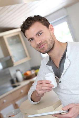 Junger Mann mit elektronischen Tablett, während Kaffee trinken Standard-Bild - 13807002