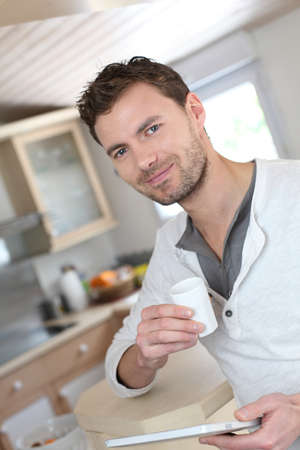 Young man using electronic tablet while drinking coffee photo