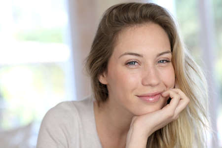 Portrait of beautiful blond woman relaxing in sofa Stock Photo
