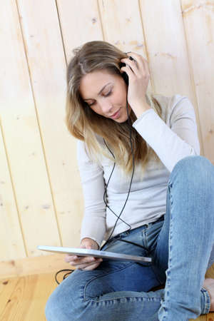 Young modern girl listening to music with electronic tablet photo