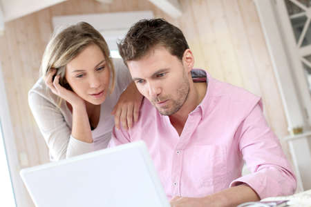 Couple at home using laptop computer photo