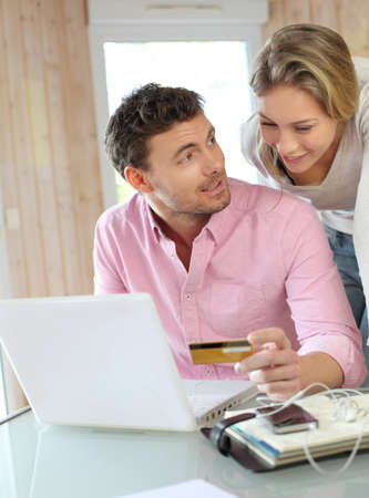 Couple using credit card to shop online photo