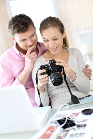 Couple at home looking at pictures on camera and laptop Stock Photo - 13806871