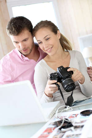 Couple at home looking at pictures on camera and laptop photo