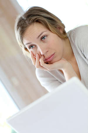Active woman in front of laptop with upset look photo