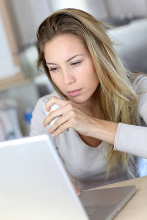 Woman checking email on laptop computer while drinking coffee  photo