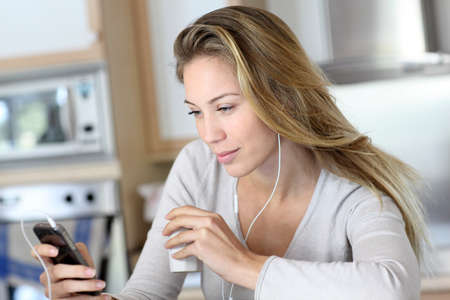 listening device: Young woman using smartphone at home with earphones
