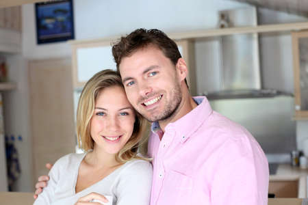 Portrait of in love couple standing in home kitchen photo