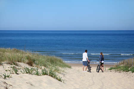 Couple with bicycles looking at the ocean photo