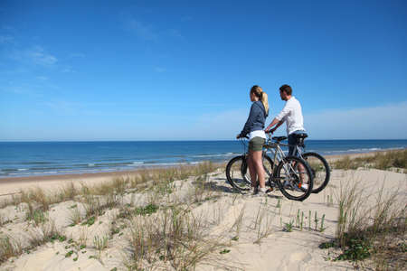 bicycles: Couple with bicycles looking at the ocean