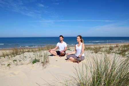 exercices: Couple doing yoga exercices on a sandy beach