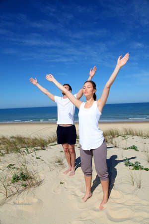 Couple meditating at the beach with arms up photo