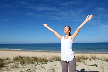 Woman breathing with arms up by the beach photo