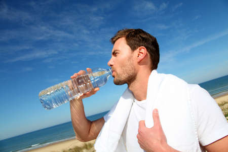 Portrait of jogger drinking water from bottle photo