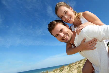 Man giving piggyback ride to girlfriend on a sand dune photo