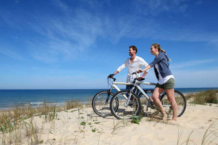 panoramic beach: Couple standing on a sand dune with bicycles Stock Photo