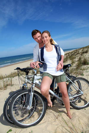 cicla: Ciclismo de pareja alegre sobre una duna de arena