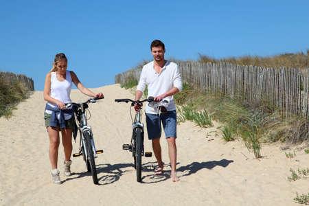 cicla: Pareja caminando en un sendero de arena con las bicicletas