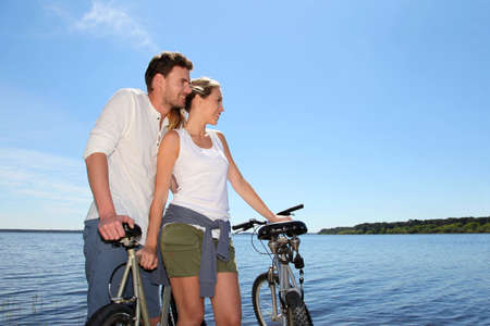 Couple standing on a bridge with bicycles photo