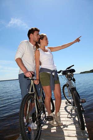 cicla: Pareja de pie en un puente con bicicletas Foto de archivo