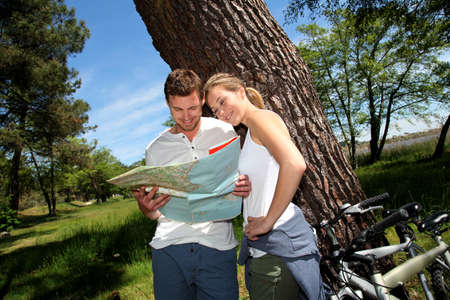 Couple on a bike ride making a stop to look at map photo