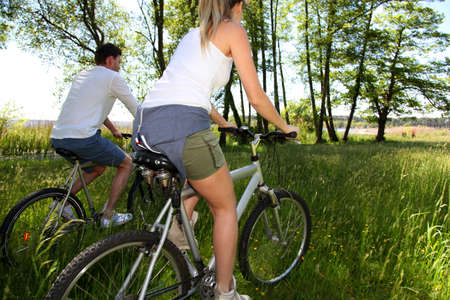 Couple riding bicycles in field by a lake Stock Photo - 13808885