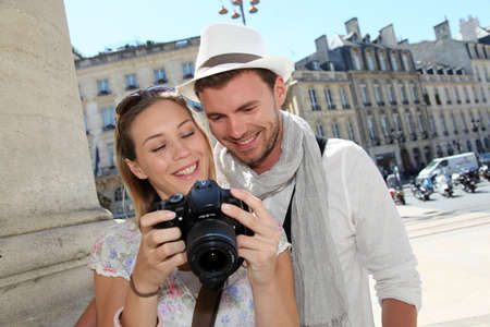 Couple enjoying taking pictures while visiting city photo
