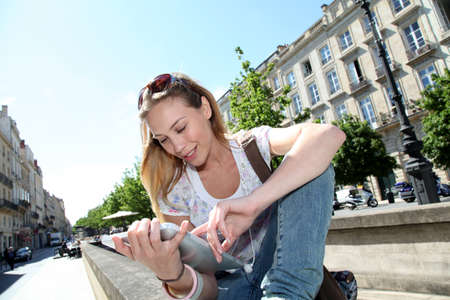 Blond woman in town using electronic tablet photo