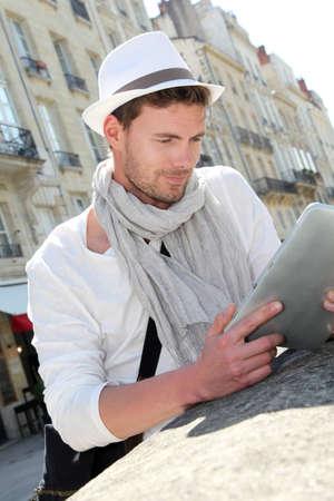 fiestas electronicas: Hombre joven con sombrero en la ciudad que usa la tableta electr�nica