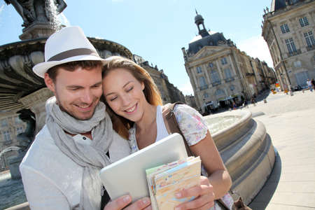 Couple standing by the Place de la Bourse with electronic tablet photo